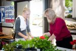 8-Dean-Gena-Cowan-right-helps-a-student-plant-a-flower-into-pots-leftover-from-a-ceramics-class.jpg